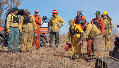 Volunteers learning how to do a controlled prairie burn